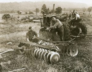 A woman sitting on a tractor and two men leaning on a piece of farm equipment and talking. They are in the middle of a field with trees in the background.