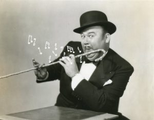 A man dressed a tuxedo, wearing a bowler hat.  He is pretending to play his cane like a musical instrument.  Musical notes have been added to the photo.