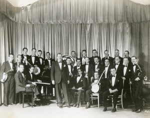A group of musicians dressed in tuxedos, holding musical instruments.
