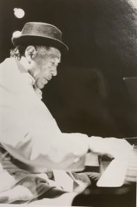 Black and white image of Duke Ellington sitting down, playing the piano.