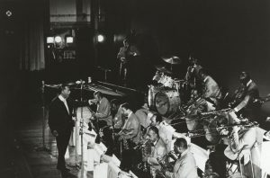 Black and white image of Duke Ellington standing and conducting his 11 piece ensemble known as the Washingtonians.