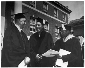 Black and white image of Sterling A. Brown (right) Duke Ellington (left) both smiling and wearing graduation caps and gowns at Howard University's 1971 commencement ceremony in Washington, D.C. Unidentified person stands to the right of Duke Ellington and is also wearing a graduation cap and gown.